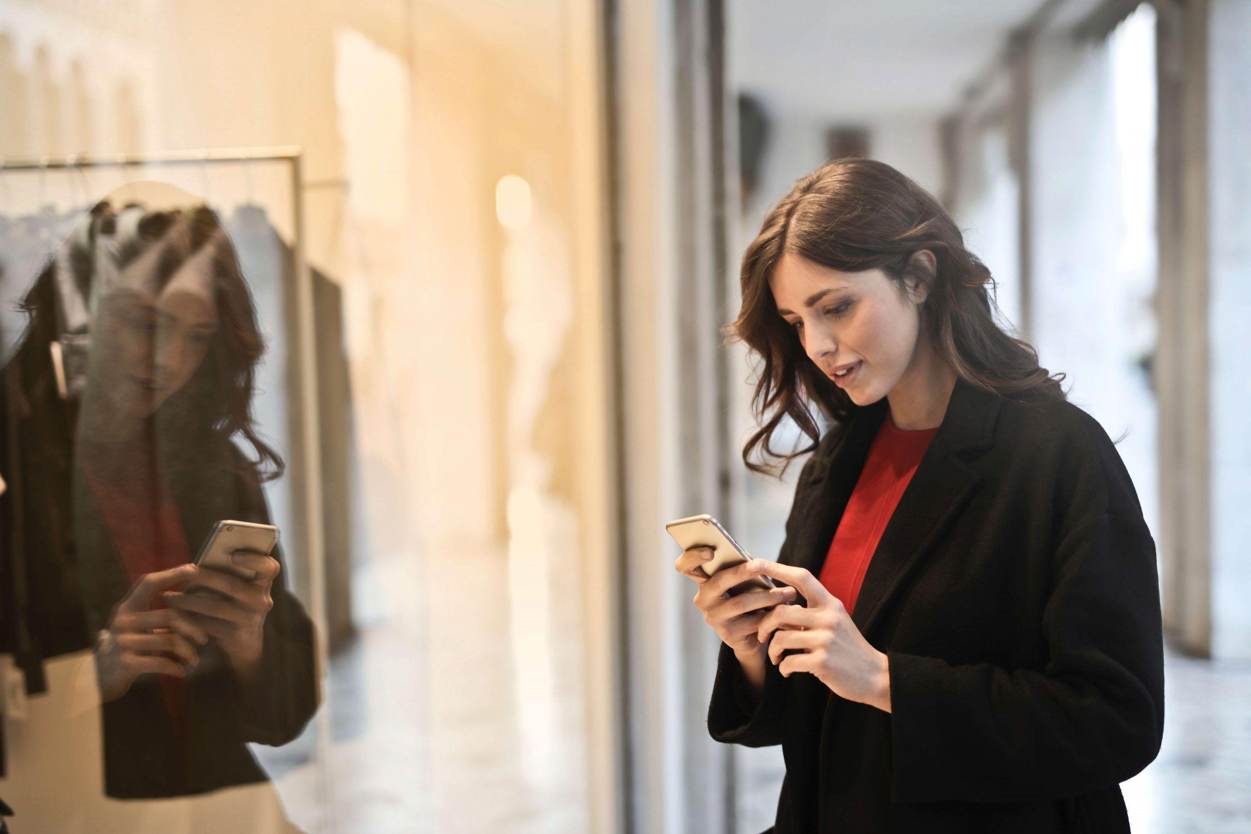 mujer mirando el movil entrando a una tienda abierta que no está en concurso de acreedores